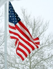 American flag flies during snowstorm